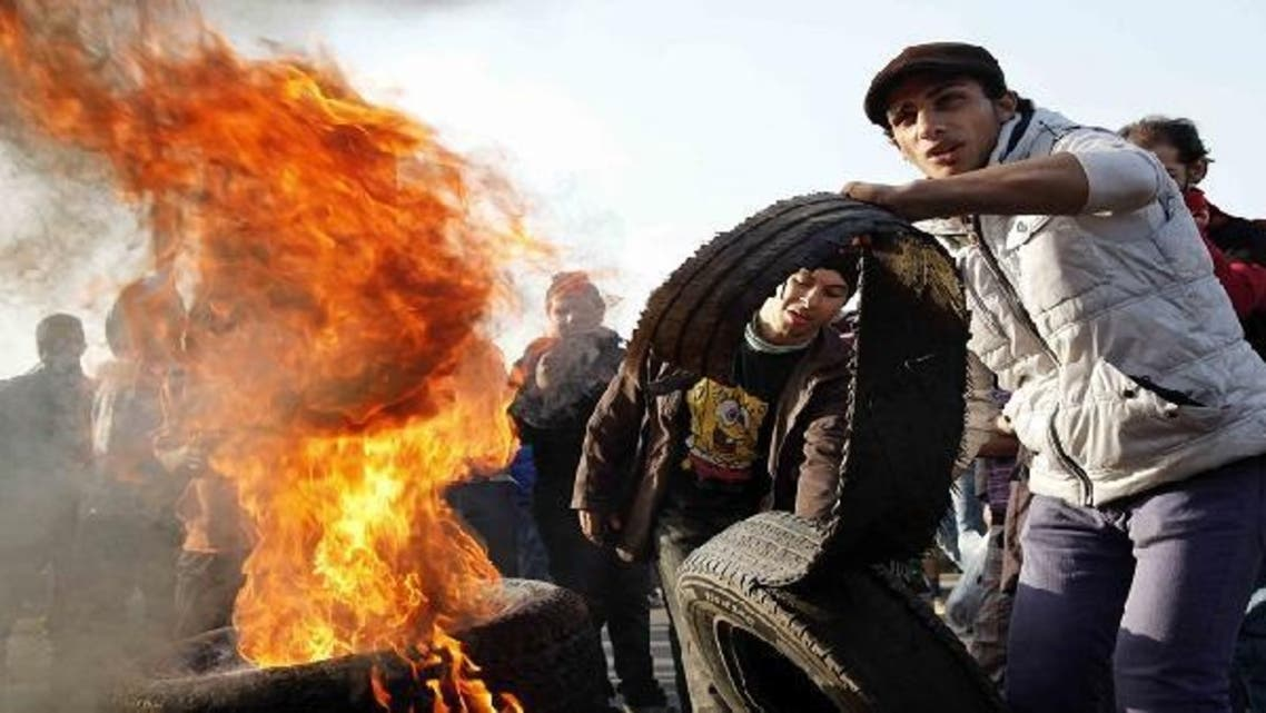 Egyptian al-Ahly football club supporters (Ultras) set fire on tires in Cairo's downtown six October bridge on Jan. 23, 2013 demanding justice for the victims of the 2012 Port Said football match killings, a few days ahead of a court ruling on the matter. (AFP)