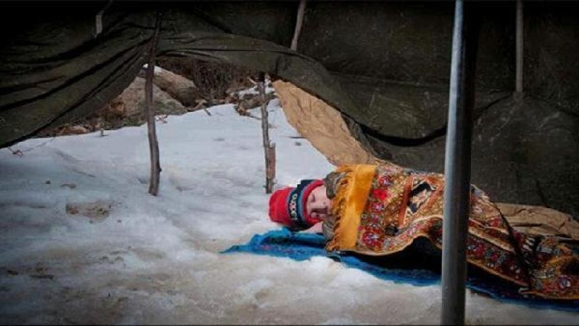 A Syrian child sleeps on the snow in a refugee camp in Lebanon\'s Bekaa Valley. (Courtesy: Facebook)