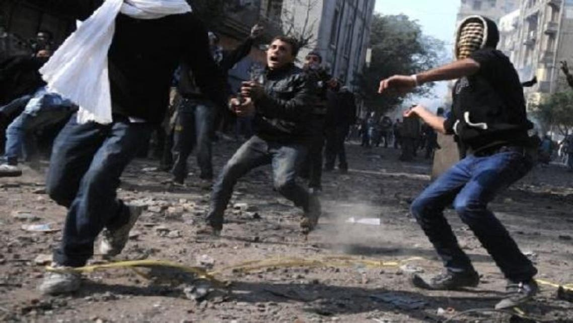 Egyptian protesters throw stones during clashes with riot police near Tahrir Square in Cairo on Nov. 23, 2011. An Egyptian court on Saturday dropped charges against 379 people involved in clashes against the police in 2011, following a decree by President Mohamed Mursi granting them amnesty, the official MENA news agency said. (AFP)