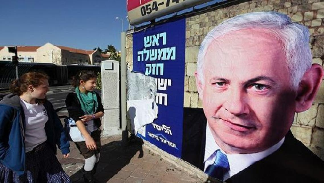 Youths look at a Likud-Yisrael Beitenu campaign poster depicting Israel's Prime Minister Benjamin Netanyahu in Jerusalem January 17, 2013. Netanyahu looks set to form a new governing coalition after next week\'s election, polls show, with the only question being whether he wants to soften its hardline contours. (Reuters)