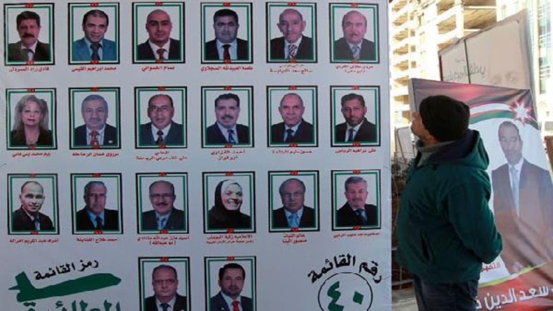 A man looks at electoral posters for parliamentary candidates in Amman January 20, 2013. (Reuters)