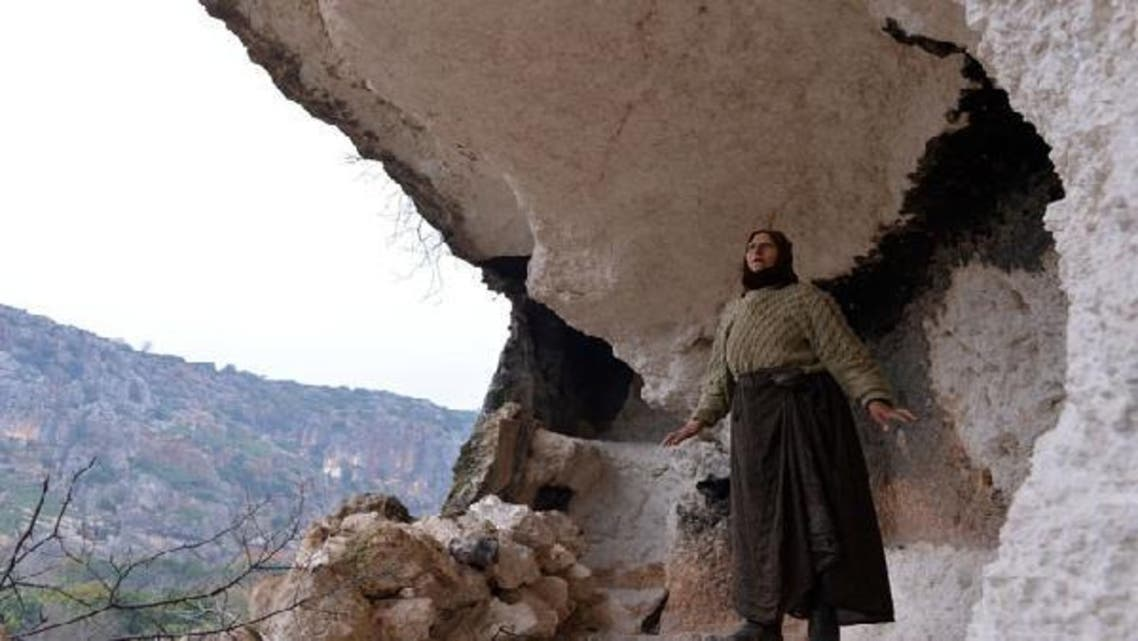 Syrian woman Najah Gafari (L), 55, who evacuated her home due to shelling by regime forces, builds a wall with rocks to protect the entrance of a cave to live with her family in Ain al-Zarka northeast of Syria on January 21, 2013. (AFP)