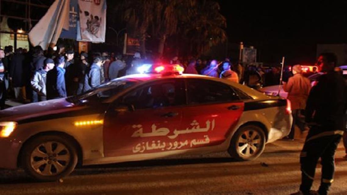 Libyans and police gather at the scene where an improvised bomb hit a police patrol car late on January 14, 2013 in a central neighborhood of the eastern city of Benghazi. (AFP)