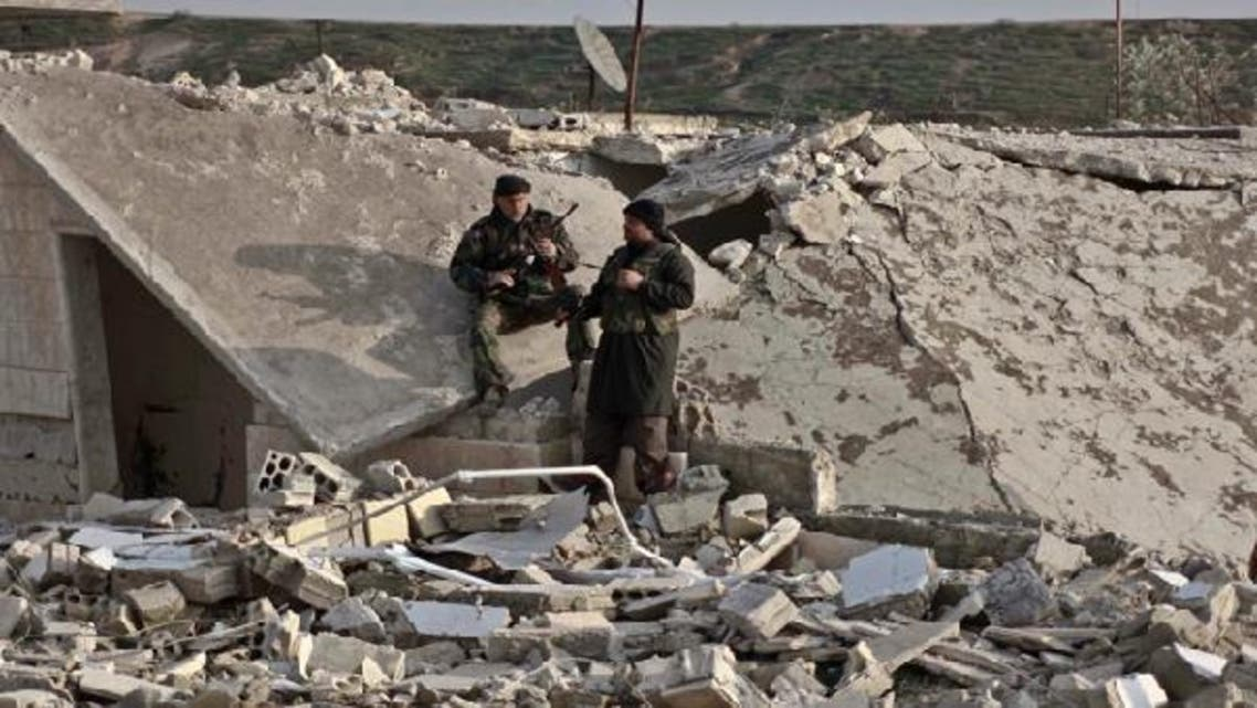 Members of Free Syrian Army take a rest near a damaged house at the front line in Hich village in Idlib January 22, 2013. (Reuters)