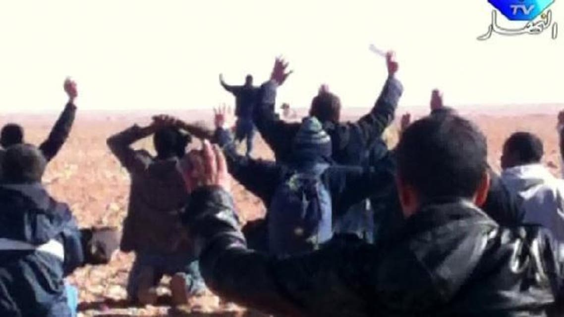A still image broadcast by Algeria\'s Ennahar TV on January 19, 2013 shows hostages surrendering to Islamist gunmen who overtook a gas facility in Tiguentourine near In Amenas in the south of the country. (AFP)