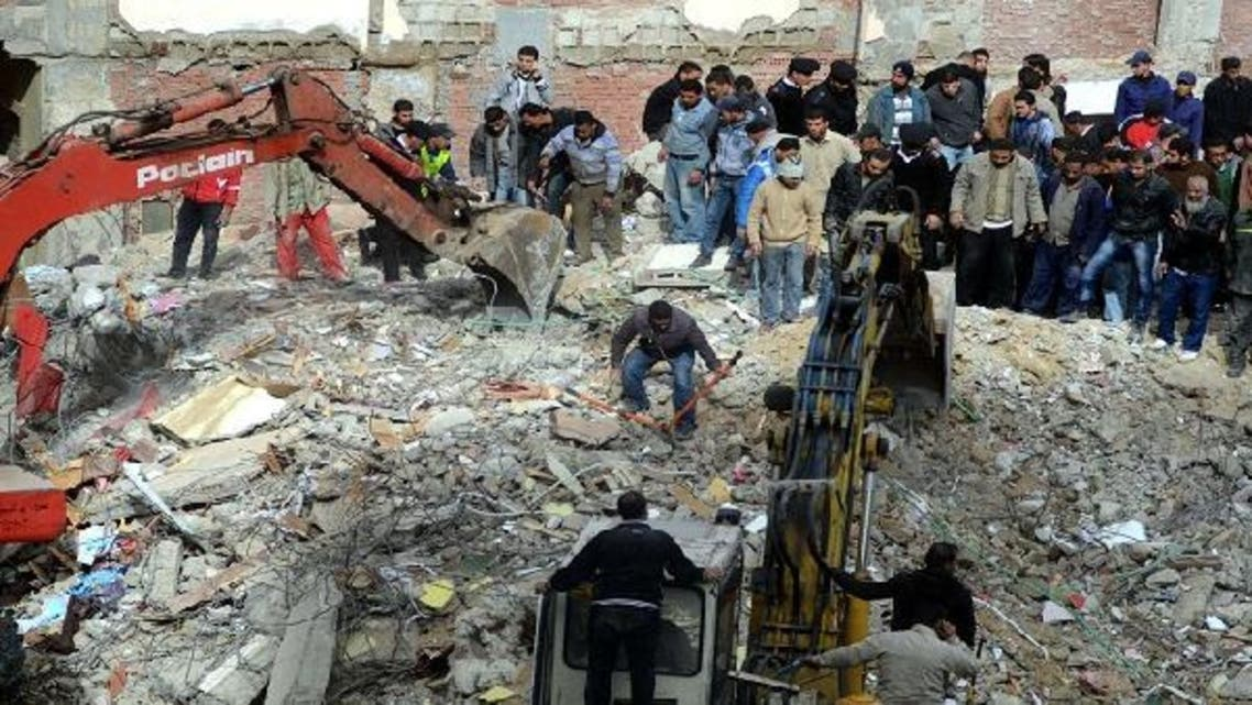 Egyptian civilians and emergency services sift through the rubble of a building housing 24 families in the Maamura district of Alexandria which collapsed in the early hours on January 16, 2013. (AFP)