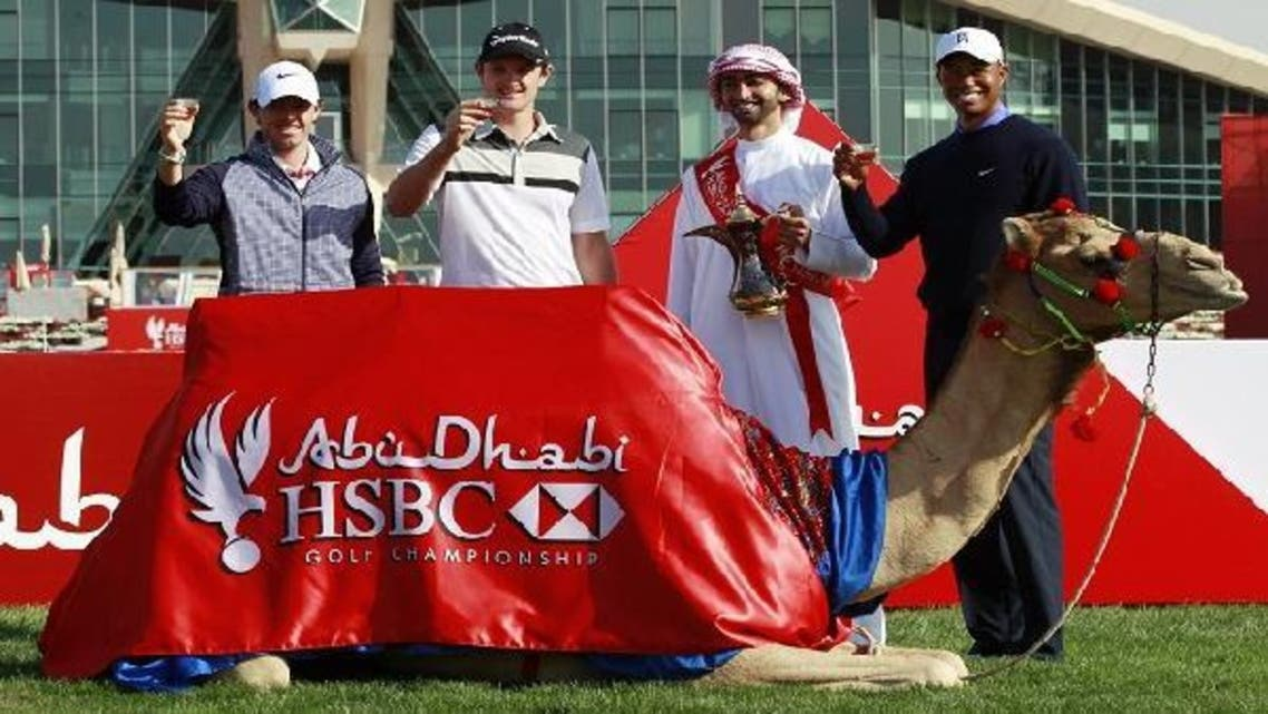 Tiger Woods (R), Justin Rose of England (2L) and world number one golfer Rory McIlroy of Northern Ireland (L) pose with an Emirati man (2R) behind a camel during 20th Abu Dhabi Golf Championship at the Abu Dhabi Golf Club on Jan. 15, 2013. (AFP)