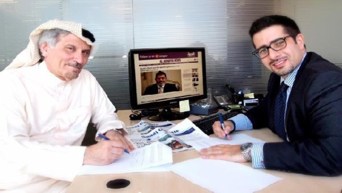 Khaled Al-Maeena, Editor-in-Chief of The Saudi Gazette  (left) and Faisal J. Abbas, Editor-in-Chief of Al Arabiya News Channel's English language portal (right) sign a content-sharing agreement. (Katherine Jane O\'Neill, Al Arabiya)