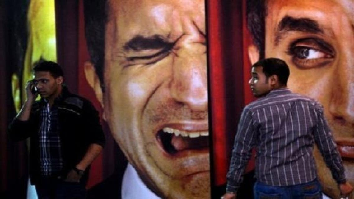 Egyptians walk past posters of Egyptian satirist Bassem Youssef outside a theatre in Cairo on Jan. 22, 2013. The Cairo cafe is packed with patrons in stitches as Youssef fires his caustic criticism at President Mohamed Mursi, but post-revolution media freedoms have proved no laughing matter for some. (AFP)