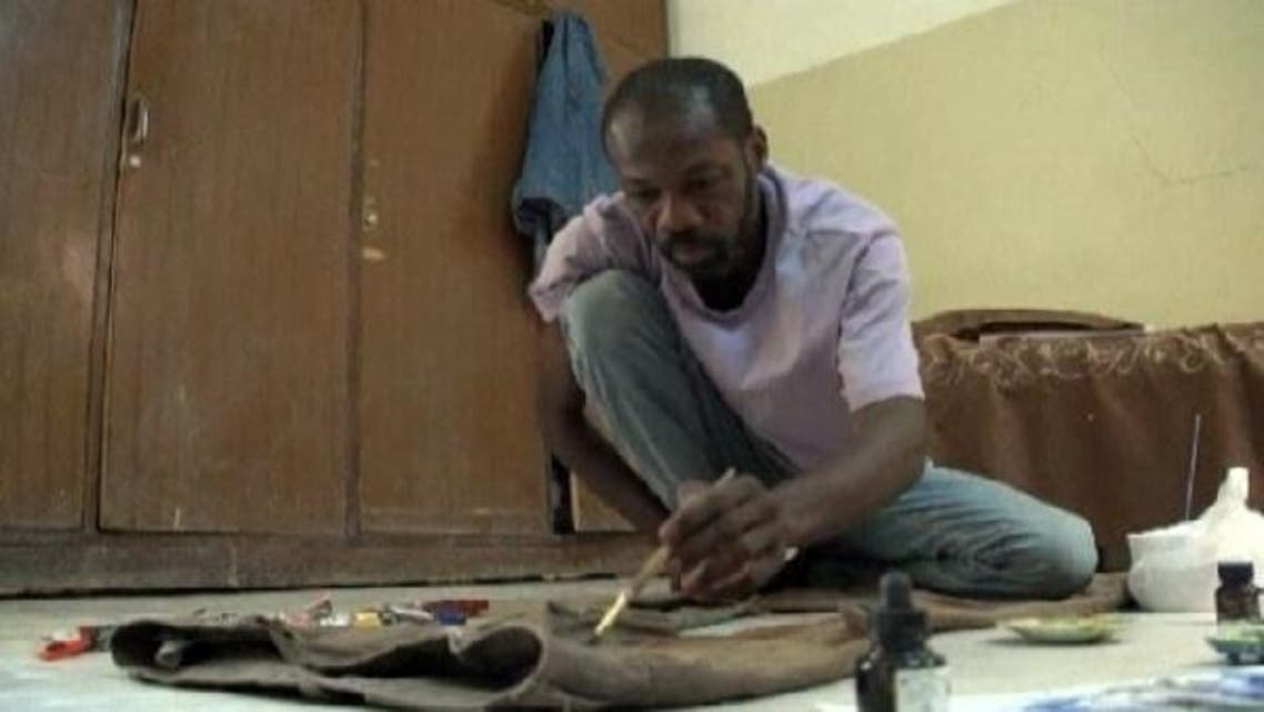 Sudanese poet and artist, Asim Ali uses his old trousers as a canvas to share memorable moments of his life. (Reuters)