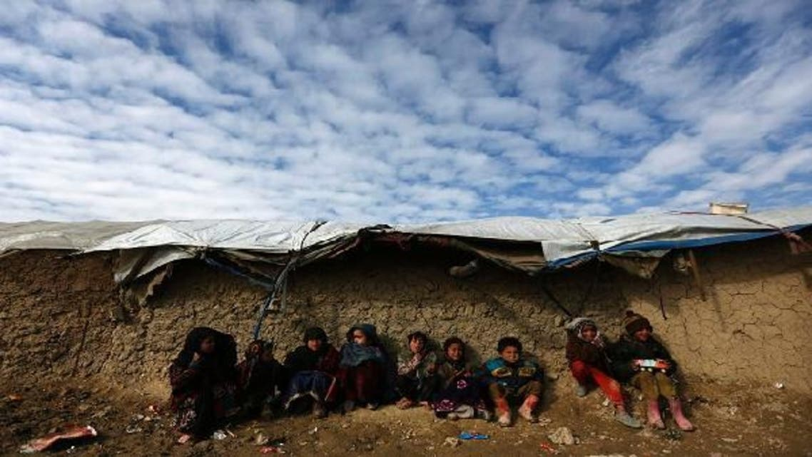 Internally displaced Afghan children sit near their shelter at a refugee camp in Kabul. (Reuters)