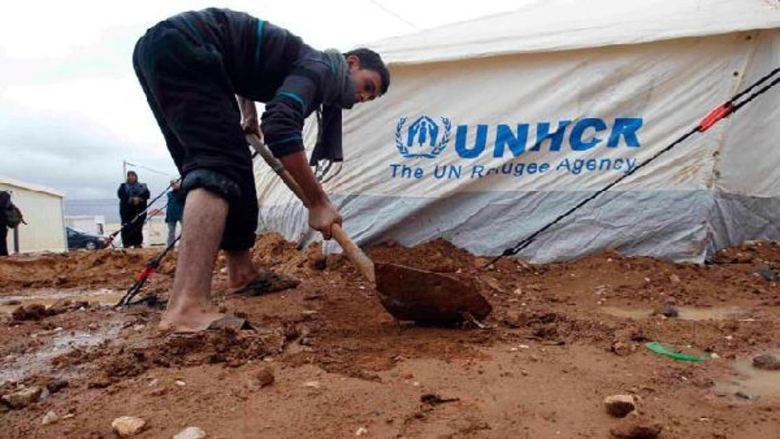 A Syrian refugee fixes his tent after heavy rain at the Al-Zaatari refugee camp in the Jordanian city of Mafraq, near the border with Syria, January 8, 2013. (Reuters)