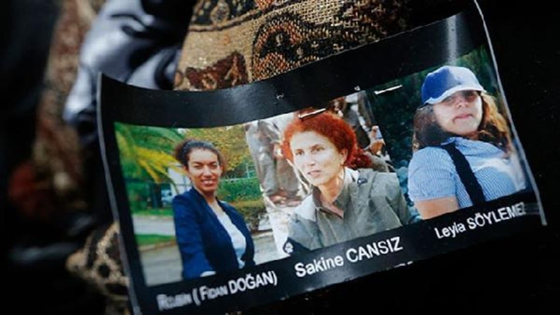 Portraits of presumed victims are seen pinned on a member of the Kurdish community\'s coat at they gather next to the entrance of the Information Centre of Kurdistan in Paris, where three Kurdish women were found shot dead. (Reuters)