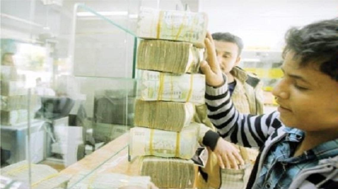 A customer receives bundles of Yemeni riyal banknotes at an exchange company in Sanaa. Yemen's fledgling economic recovery is good news for efforts to restore political stability in the country. (Reuters)
