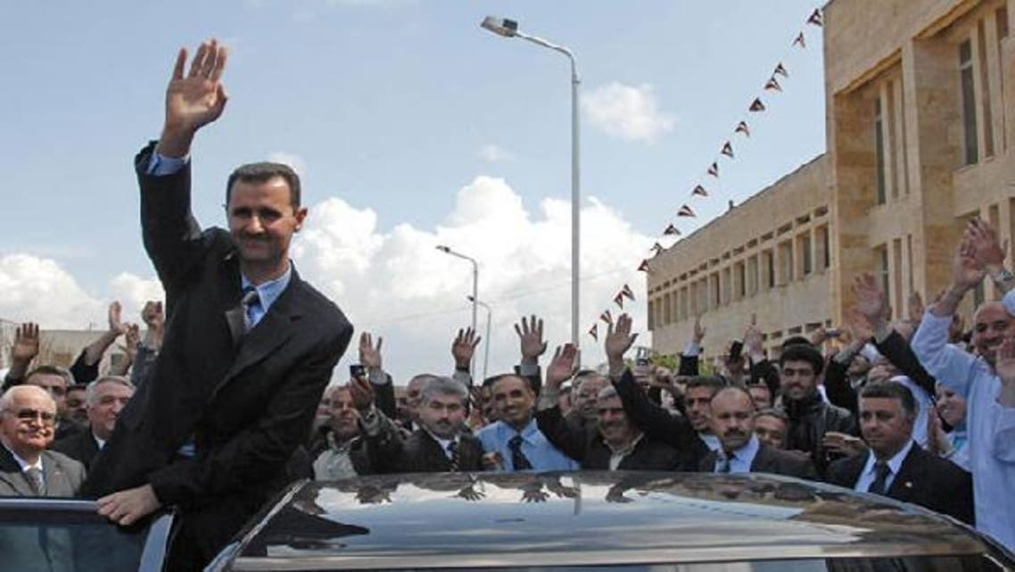 Syrian President Bashar al-Assad waves to the crowd. (Reuters)