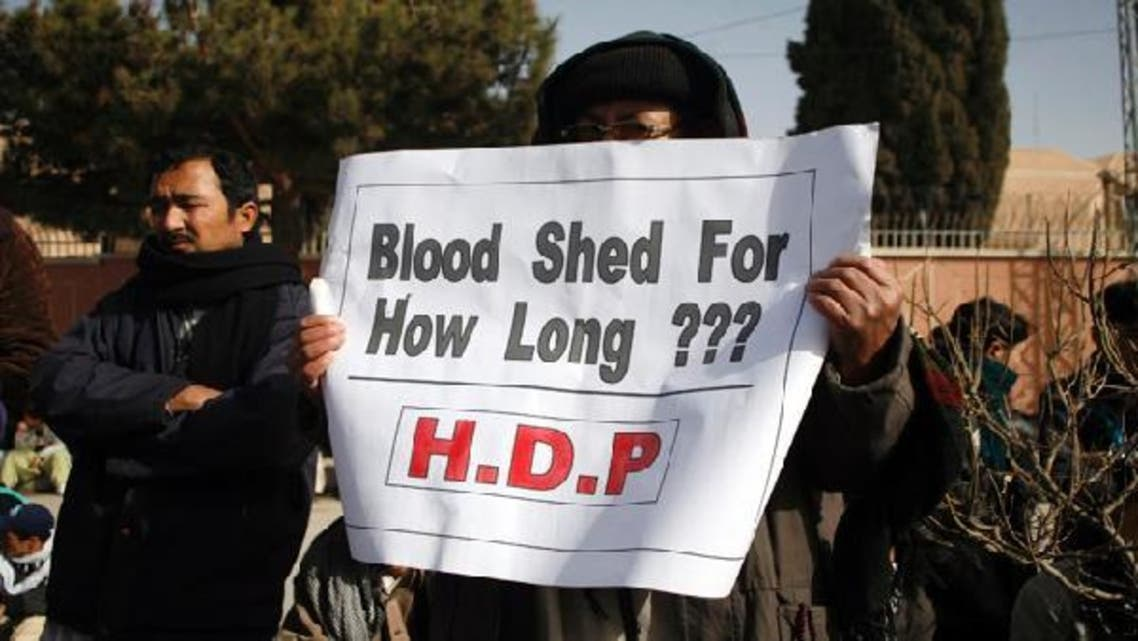 A supporter of Hazara Democratic Party holds a sign during a sit-in in front of a police office to protest against last Thursday\'s twin bomb attack in Quetta January 12, 2013. (Reuters)