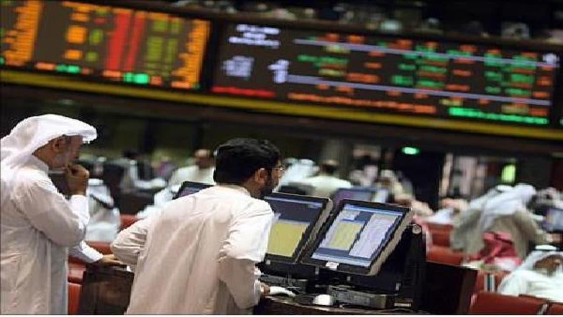 متداولون يراقبون أسعار الأسهم في بورصة الكويت