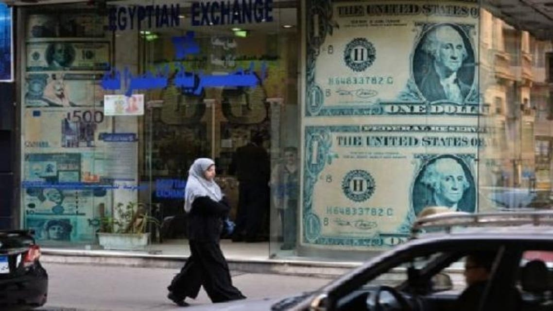 A file photo shows a woman walks past a foreign exchange store in Cairo, Egypt. (AFP)