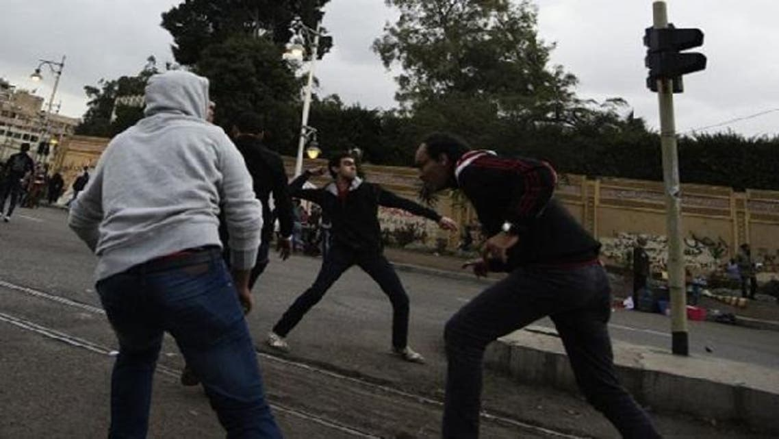 Supporters of Egyptian President Mohammed Mursi clash with anti-Mursi protesters outside the presidential palace in Cairo last December. (AFP)