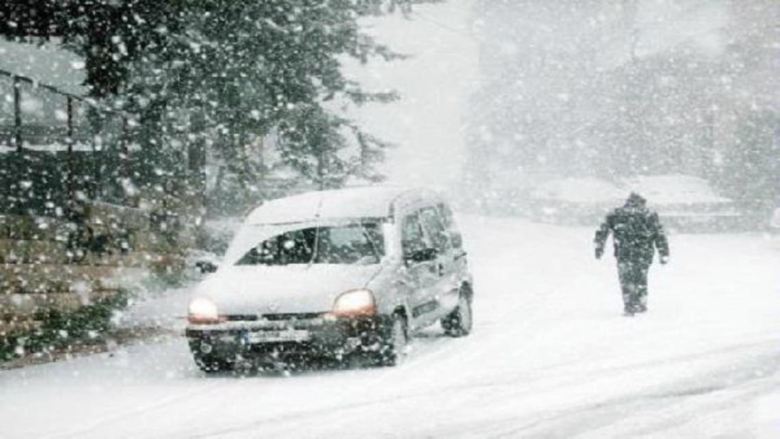 A car drives through the snow in Aley area, eastern Lebanon on Wednesday. The storm batters Lebanon, Jordan, Turkey, Israel and the Palestinian Territories. (Reuters)
