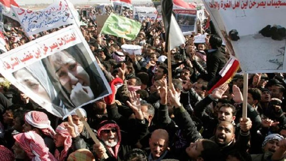 """Protesters take part in a demonstration in Ramadi, 100 km (62 miles) west of Baghdad, December 26, 2012. Tens of thousands of Sunni Muslims blocked Iraq's main trade route to neighboring Syria and Jordan in a fourth day of demonstrations on Wednesday against Shiite Prime Minister Nuri al-Maliki. The banner (bottom left) reads, """"Female prisoners ask loudly, 'Where is the anger of honorable people?' (Reuters)"""