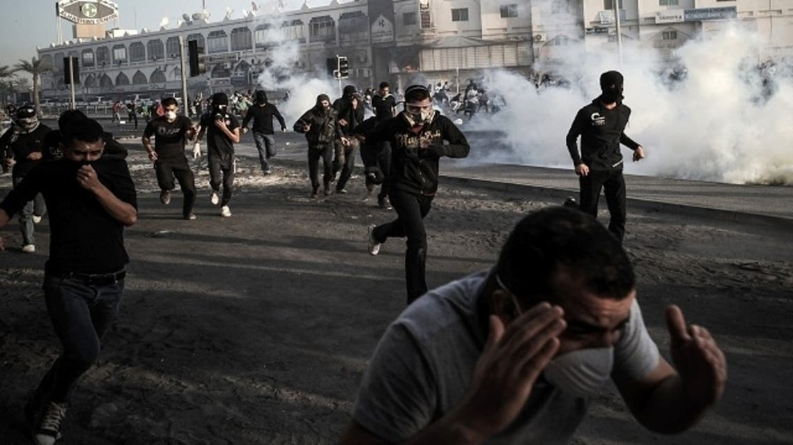 Bahraini protesters rush away after riot police fired tear gas during clashes following the funeral of a teenager killed in protests marking the second anniversary of a Shiite-led uprising, on Feb. 16, 2013 in west of Manama. (AFP)