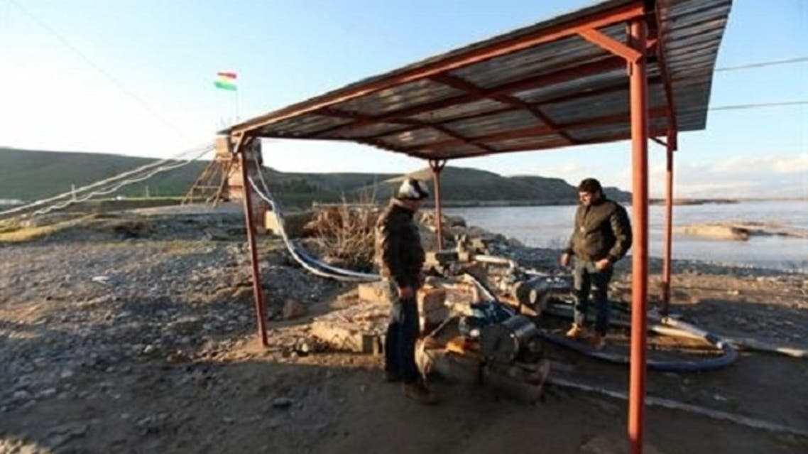 Iraqi Kurds stand near pipes that feed diesel from a pumping station in Iraqi Kurdistan to Syria on the Iraqi bank of the river Tigris at the Iraqi-Syrian border near the Dohuk province, Feb. 2, 2013. (Reuters)