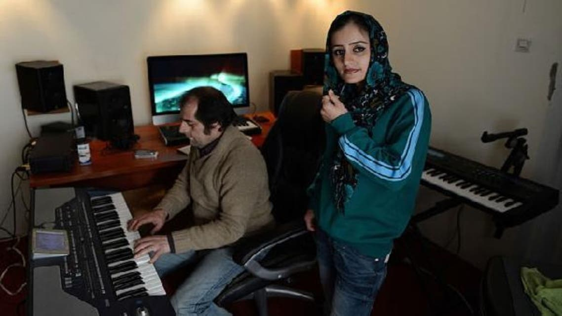 This picture shows Soosan Feroz, 23, (R) Afghanistan\'s first female rap musician, looking on as she practices with Afghan pop musician Farid Rastagar at a recording studio in Kabul. (AFP)