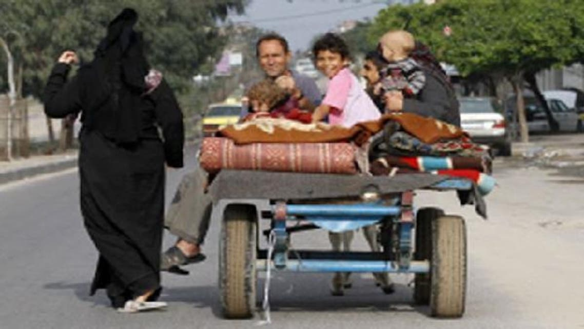Members of a Palestinian family ride on a four-wheeled cart drawn by a donkey in Gaza City as displaced Gazans returned to their homes after an eight-day conflict on November 22, 2012. (AFP)