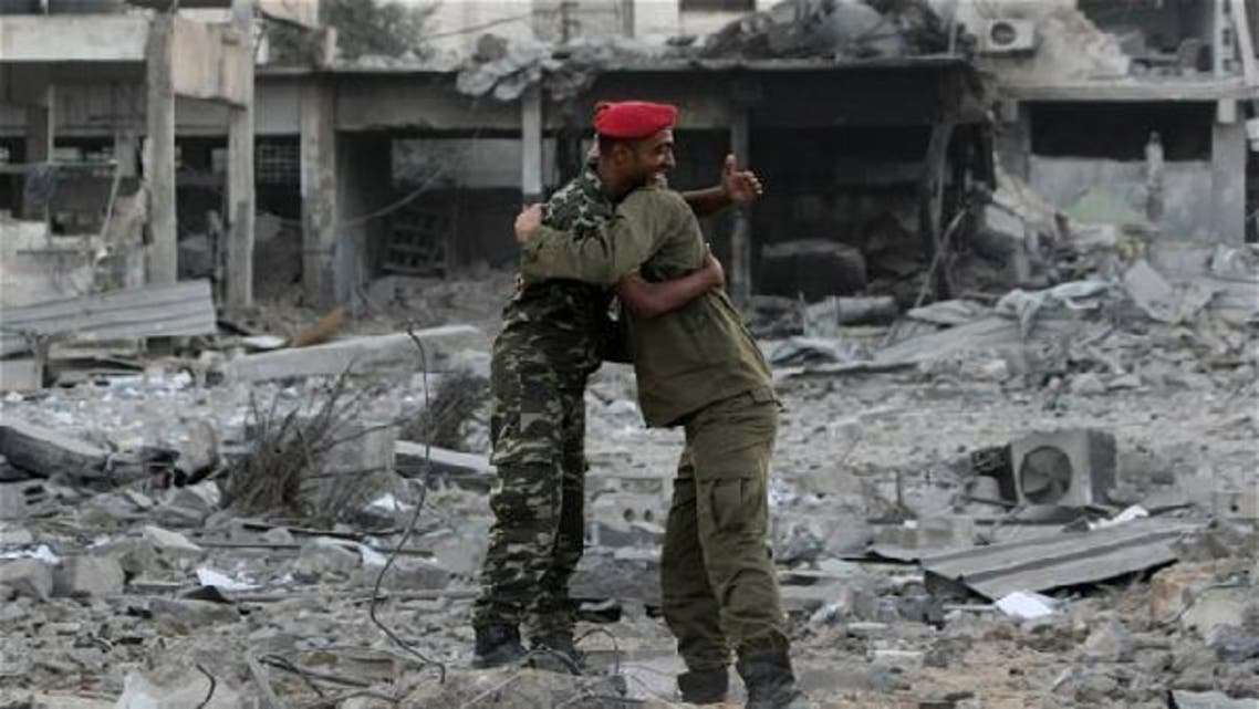 Hamas police officers embrace after their return to their destroyed Al-Saraya headquarters in Gaza City. (AFP)