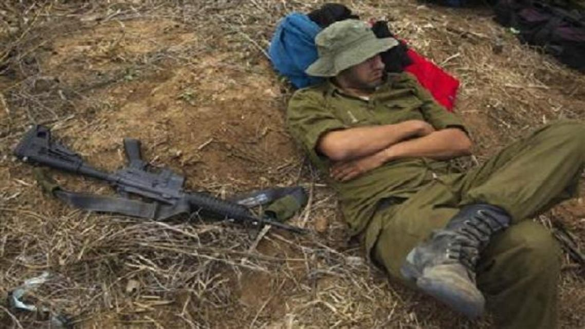 An Israeli reservist soldier rests beside a weapon as he waits in a field before heading home, near the border with the northern Gaza Strip Nov. 22, 2012. A ceasefire between Israel and Hamas took hold on Thursday with scenes of joy among the ruins in Gaza over what Palestinians hailed as a victory, and both sides saying their fingers were still on the trigger. (Reuters)