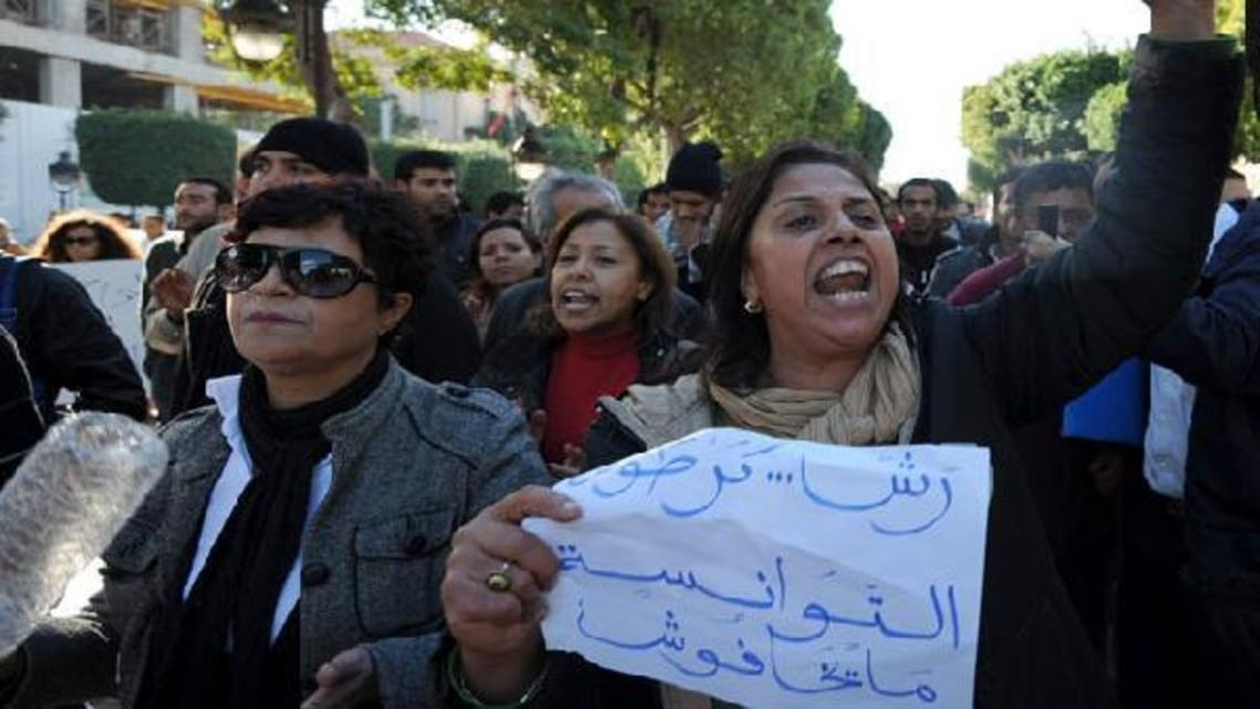 """Tunisian protester holds a poster in the country's capital that reads: """"Tunisians are not afraid"""" as she demonstrates in solidarity with the inhabitants of the southwestern town of Siliana on Nov.28, 2012. (AFP)"""