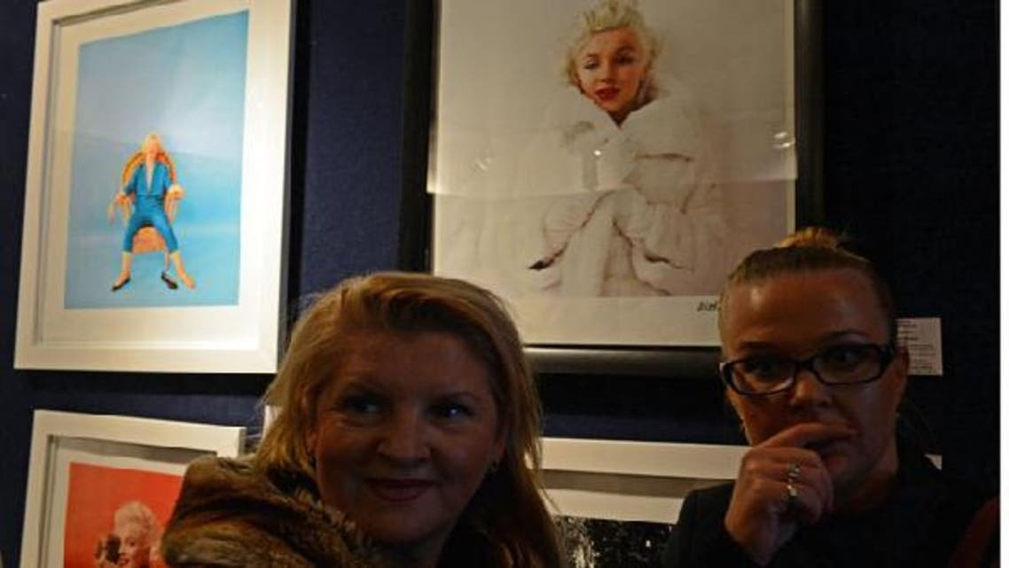 Two women stand in front of pictures showing Marilyn Monroe during an auction of photographs taken by late celebrity photographer Milton Greene on November 8, 2012 in Warsaw, Poland. (AFP)