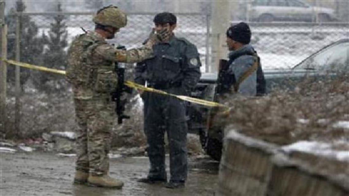 ایک افغان پولیس اہلکار اور نیٹو فوجی بم دھماکے کی جگہ پر کھڑے ہیں