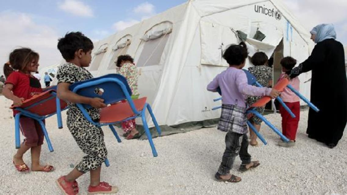 Young Syrian refugees carry their chairs into a classroom at a UNICEF-run school in the al-Zaatari refugee camp in the Jordanian city of Mafraq near the border with Syria. (AFP)