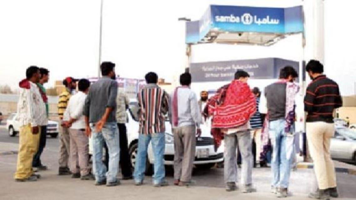 عمال في انتظار أمام أحد أجهزة الصراف الآلي حيث تقدر السعودية حجم الحوالات السنوية من العمالة إلى الخارج بنحو 100 مليار ريال