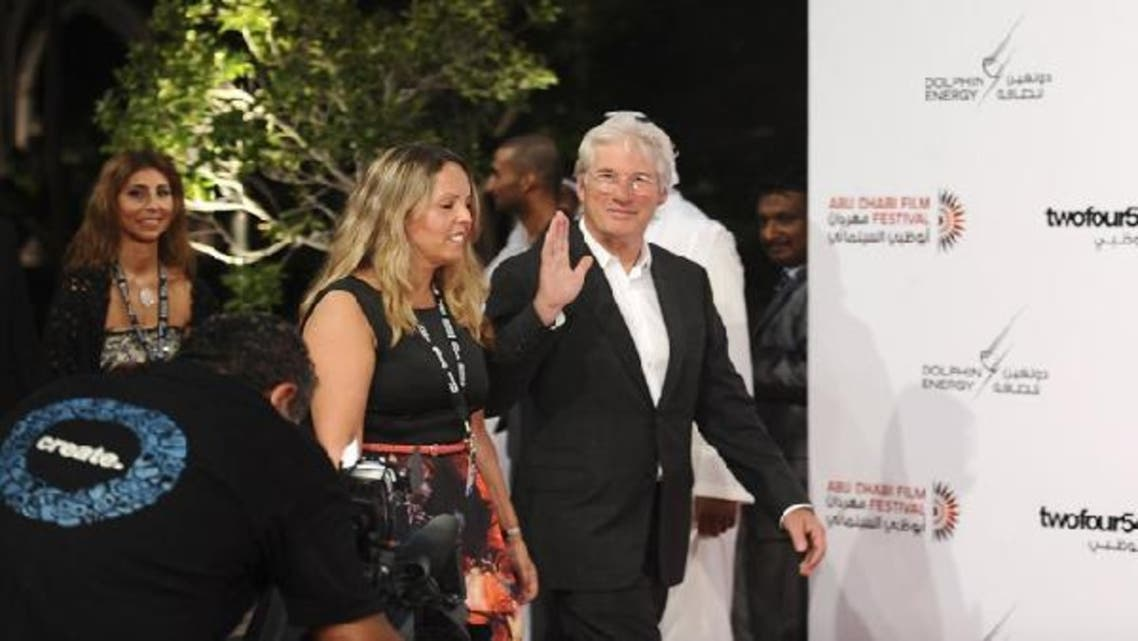 U.S. actor Richard Gere arrives on the red carpet with a festival organizer during the opening of the 6th Abu Dhabi Film Festival. (Reuters)