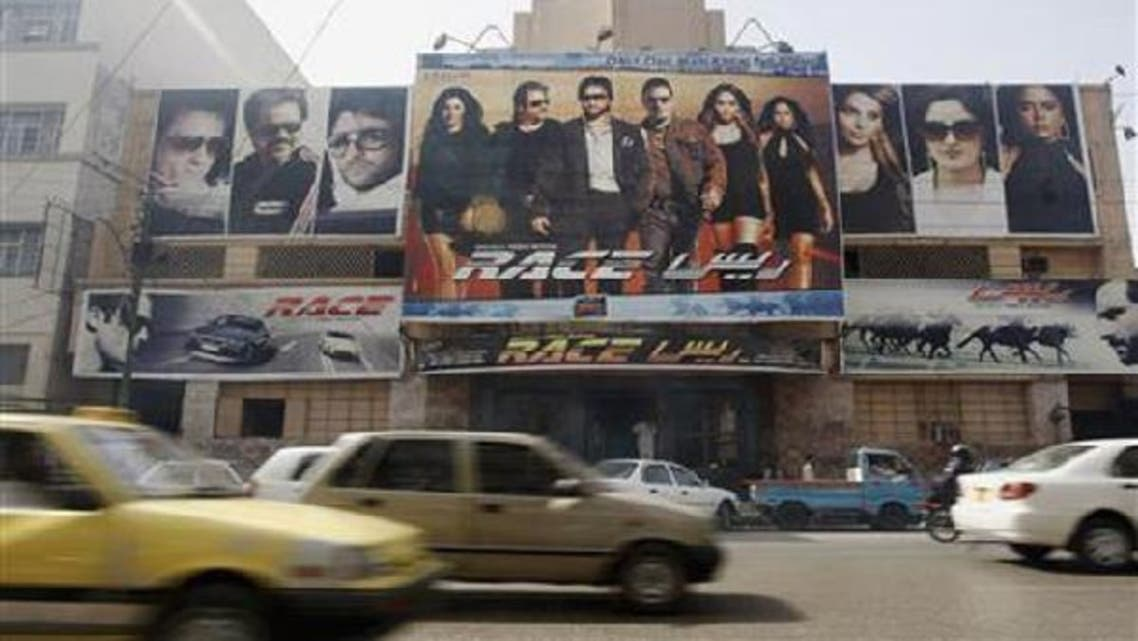 Vehicles are driven past a cinema displaying Indian movie posters in Karachi April 21, 2008. (Reuters)
