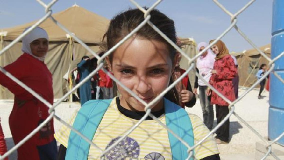 A Syrian refugee girl looks out from behind a fence as she attends school at the Zaatari refugee camp in the Jordanian city of Mafraq, near the border with Syria. (Reuters)