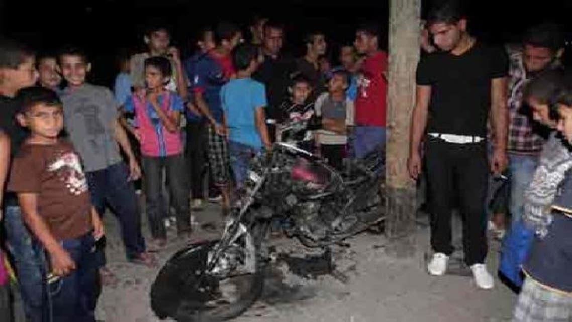 فلسطینی شہری اسرائیلی میزائل حملے کا نشانہ بننے والے موٹر سائیکل کا ڈھانچہ دیکھ رہے ہیں
