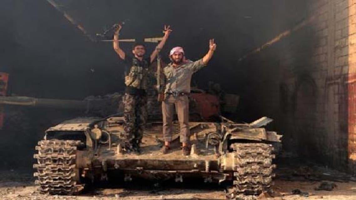 جیش الحر کے دو رکن شامی فوج سے چھینے گئے ایک ٹینک پر فتح کا نشان بنائے کھڑے ہیں۔