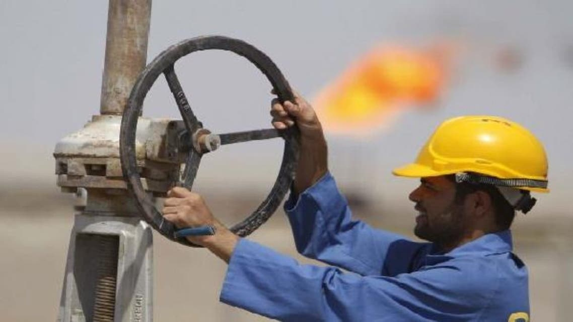 A worker adjusts a pipe at the Nassiriya oilfield in Nassiriya, 300km (185 miles) southeast of Baghdad. (Reuters)