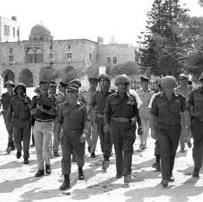 Israeli defense minister Moshe Dayan tours the old city with his generals after occupying it. (AP)