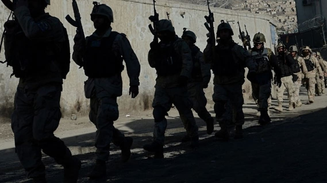 Afghan commandos walk down a road near the Kabul police headquarters building after a clash between Afghanistan forces and Taliban fighters in Kabul on January 21, 2013. (AFP)