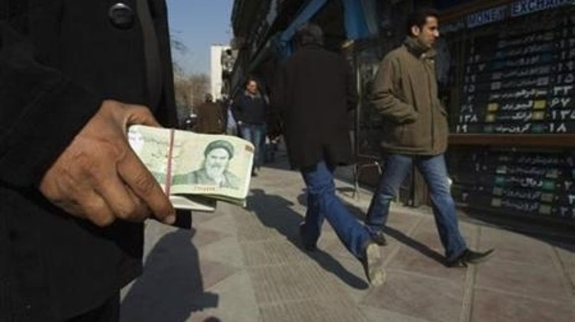 A money changer holds Iranian rial banknotes as he waits for customers in Tehran's business district January 7, 2012. (Reuters)