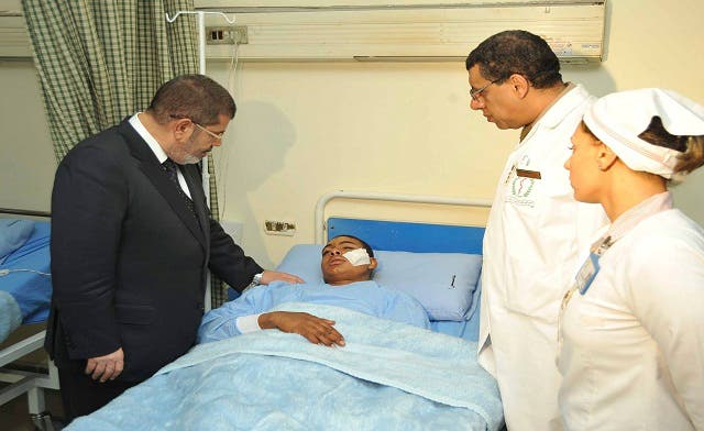 Egyptian President Mohammed Mursi talks with a soldier injured in a train accident at a hospital in Cairo January 15, 2013.  (Reuters)