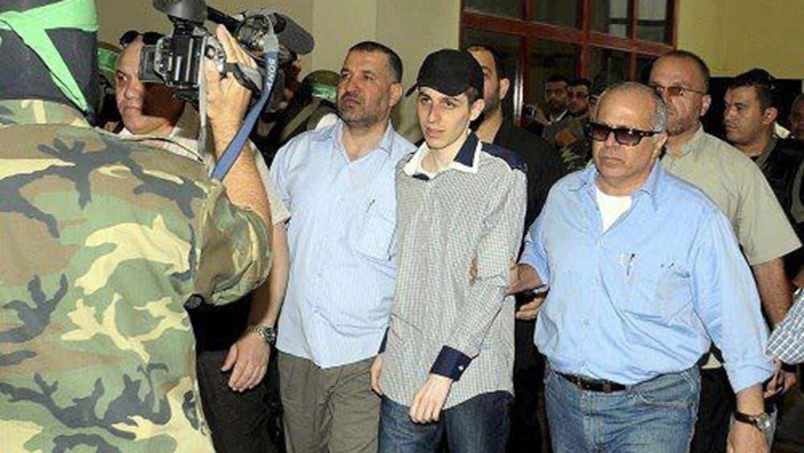 شاليط متوسطاً كلاً من أحمد الجعبرى على اليسار ومدير المخابرات المصرية الحالى رأفت شحاتة