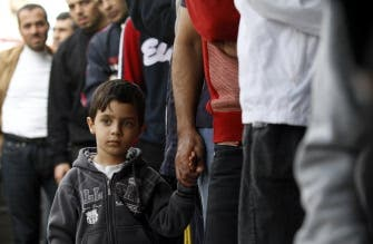 A Palestinian boy waits with a relative in a queue to buy bread in Gaza City on Nov. 17, 2012. (AFP)