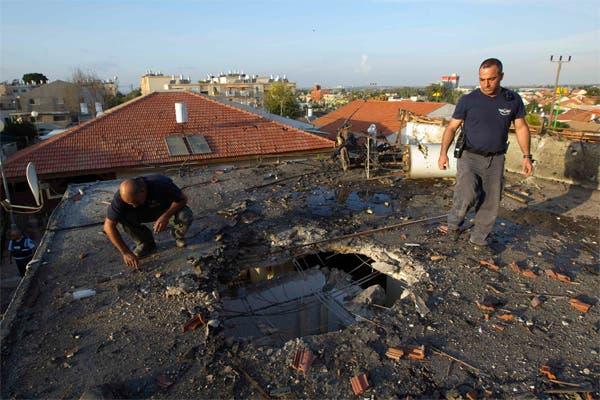 عنصري شرطة اسرائيليين يتفقدان آثار صاروخ اطلق من غزة