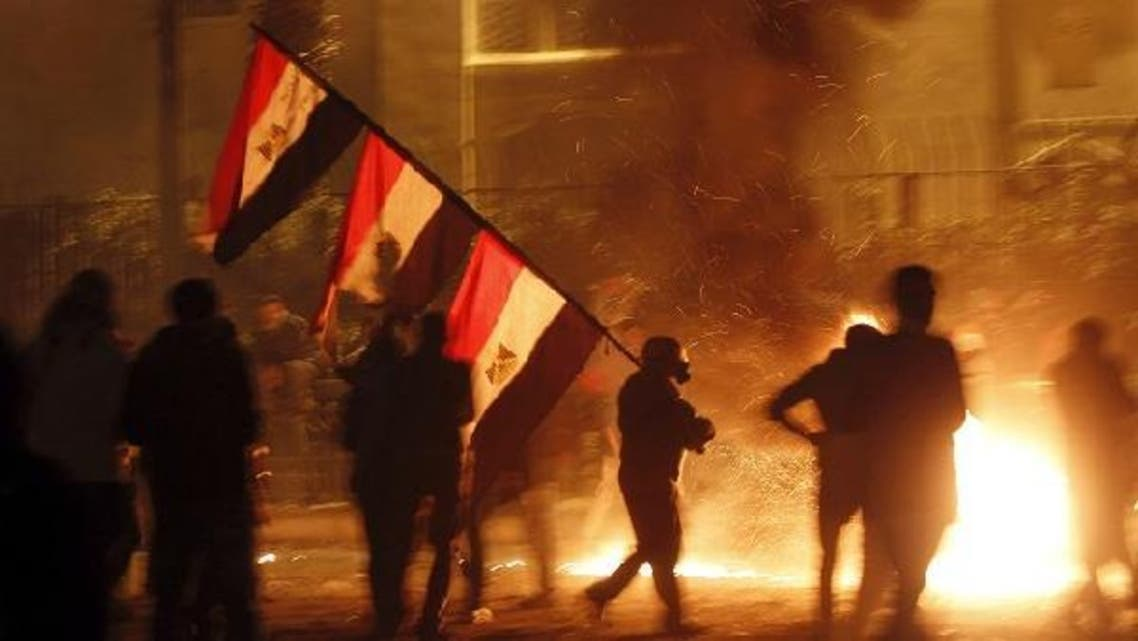 A protester opposing Egyptian President Mohamed Mursi carries national flags while walking near flames from Molotov cocktails thrown by protesters during clashes with riot police at the front road of Maspero, the Egyptian Radio & Television Union Headquarters, near Tahrir Square in Cairo January 25, 2013. (Reuters)